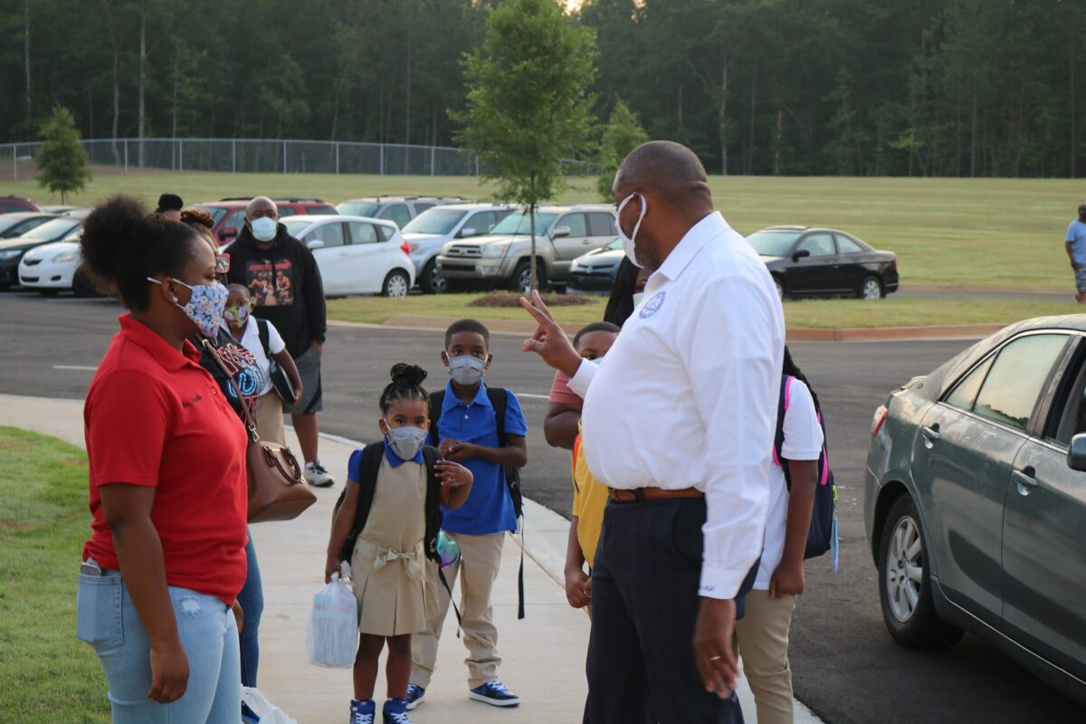 Superintendent Dr. Morcease Beasley speaks with kids and parents in parking lot on first day of school.